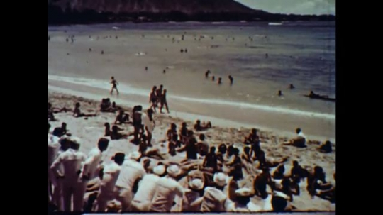 United States: 1960s: people on beach. Man surfs in sea. People visit temple in Japan. Buddhist statue in gardens. People walk in city street