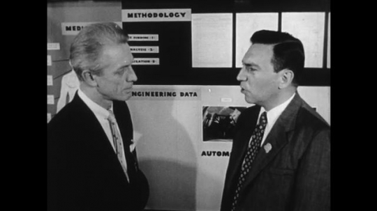 UNITED STATES: 1950s: two men talk by medical poster presentation at conference. Graph shows injury through car accident.