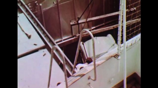 UNITED STATES: 1950s: Car loaded into lower deck of ship. Mariners sit in mess.