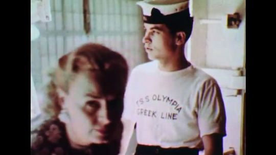 UNITED STATES: 1950s: Sailor welcomes passengers on to ship. Flag of ship. Tender boats approach ship. People say goodbye on boats.