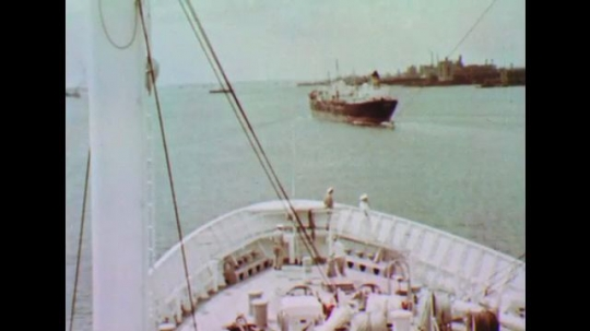 UNITED STATES: 1950s: People on deck of ship. Ship passes Statue of Liberty. Ship flies flag. Man steers boat.
