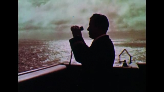 UNITED STATES: 1950s: Man on ship looks through binoculars. Waves behind ship. Steam from ship.