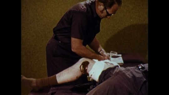 United States: 1970s: man unfolds long bandage. Man applies bandage to knee wound.