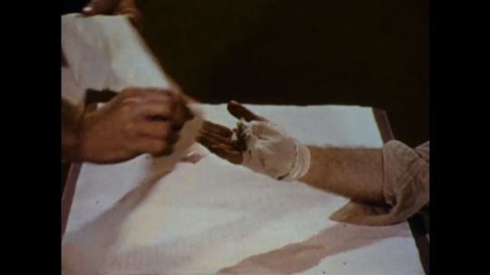 United States: 1970s: patient holds hand above table. Man applies bandage to injured hand. Man criss crosses bandage on hand. Man ties knot over wrist.