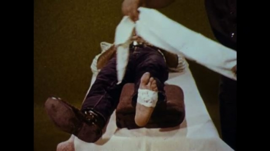United States: 1970s: man with foot wound lies on bed. Man applies bandage to foot wound.