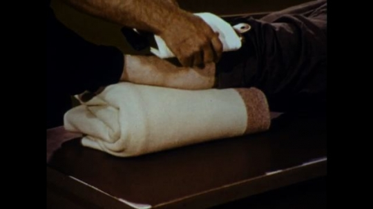 United States: 1970s: man applies compress to elevated leg. Man wrings out hot water from towel. Patient lies on bed on front. Man applies hot towel to man's back.