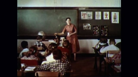 UNITED STATES 1950s: Young boy student comes to front of classroom with teacher, two girls talk at their desks, clock shows 10:14.