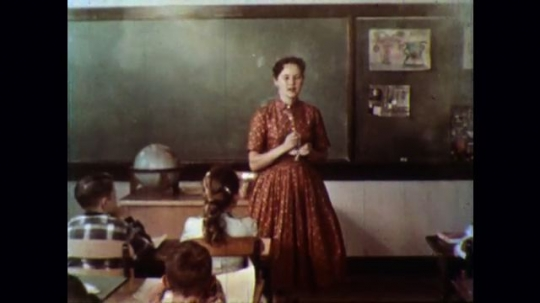 UNITED STATES 1950s: Teacher conducts song at front of classroom while smokes pours in, fire trucks quickly leave station.