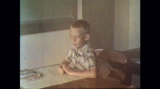UNITED STATES 1950s: Young boy looks around nervously while sitting at desk as smoke fills the room, then he sneaks out of a backdoor.