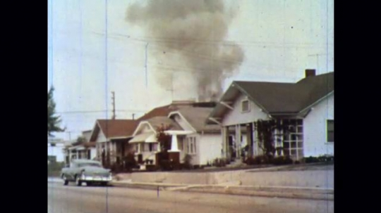 UNITED STATES 1950s: Smoke pours over the rooftops of a neighborhood. Smoke billows in front of a clock. Burning fire.
