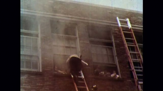 UNITED STATES 1950s: Firefighters rescue children from a burning building using ladders.