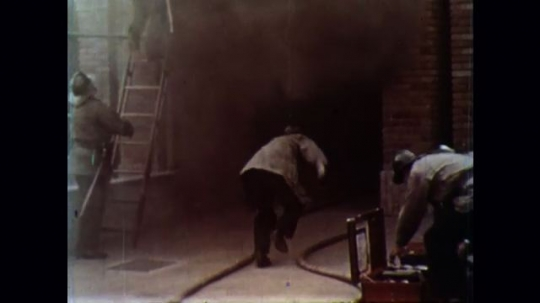 UNITED STATES 1950s: Firefighters rescue children from a burning building and hustle to put out the fire.