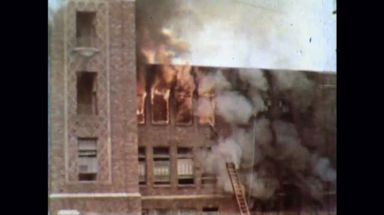 UNITED STATES 1950s: Large building on fire, smoke and flames coming out of windows. Firefighters spray it with hose.