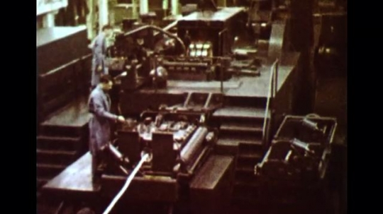 UNITED STATES 1960s: Long shot, men operating machines in factory.