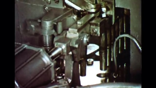 UNITED STATES 1960s: Close up, bolts forming in machine / Machine threading bolts / Bolts on conveyor belts.