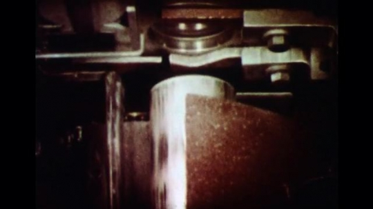 UNITED STATES 1960s: Slow motion close up of machine forming aluminum cans.