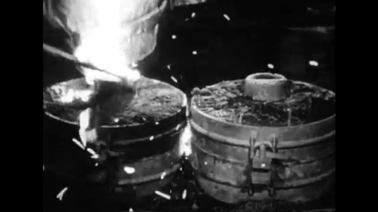UNITED STATES: 1950s: flames in iron mongers workshop. Man works with molten metal.