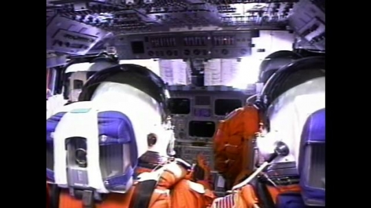 UNITED STATES: 2000s: Astronauts inside space shuttle cabin. View over astronauts' shoulders. Astronauts gives thumbs up. View of shuttle taking off. Shaking as shuttle launches