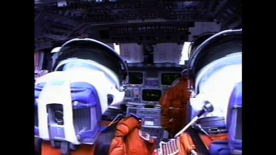 UNITED STATES: 2000s: Astronauts sit inside space shuttle cabin during flight. Monitors flicker. View over astronauts' shoulders. Astronaut reads notes.