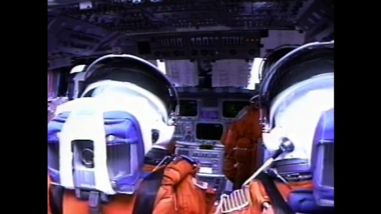 UNITED STATES: 2000s: Astronauts inside space shuttle cabin. Monitors flicker. View over astronauts' shoulders. Astronaut checks watch.  Astronats arrive in space. Astronauts adjust dashboard
