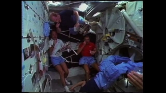 UNITED STATES: 1980s: astronauts throw food across cabin. Fish biscuits in bag in space. Astronauts have fun in space.