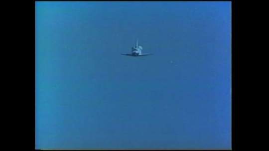UNITED STATES: 1980s: Space shuttle returns to Earth. Landing gear lowers on space shuttle. Shuttle lands on runway.