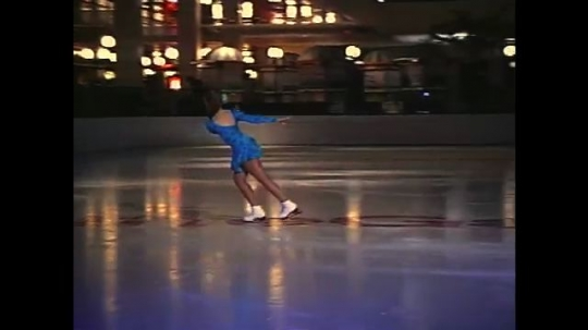 UNITED STATES: 1990s: lady ice skates and spins on axis. Slow motion ice skater