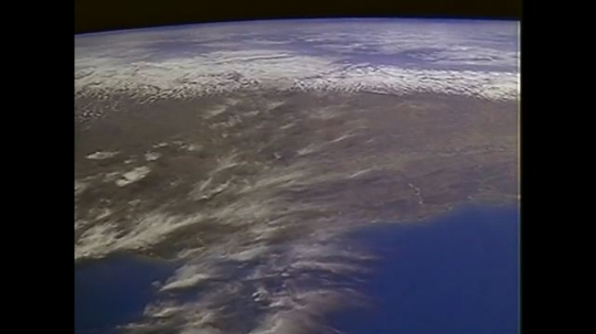 UNITED STATES: 1990s: view of Earth from space. Animation of satellite tethered to shuttle.
