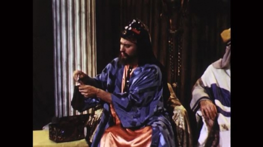 UNITED STATES: 1950s: temple elder counts pieces of silver. High priest talks to Judas. Man pays Judas.
