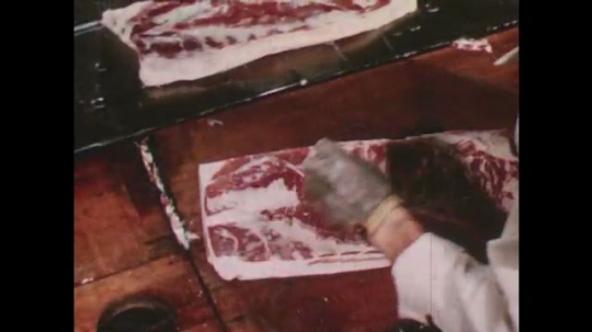 United States: 1950s: man takes meat from conveyor belt. Man cuts meat. Man pulls rack of meat towards him