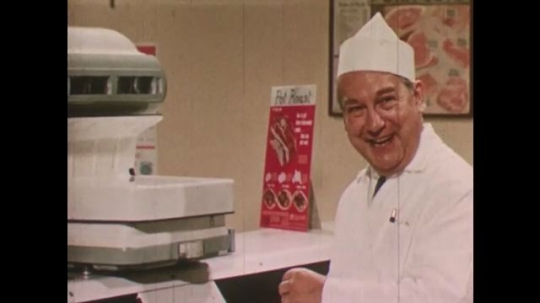 United States: 1950s: Butcher smiles. Butcher examines meat. Lady talks to butcher.