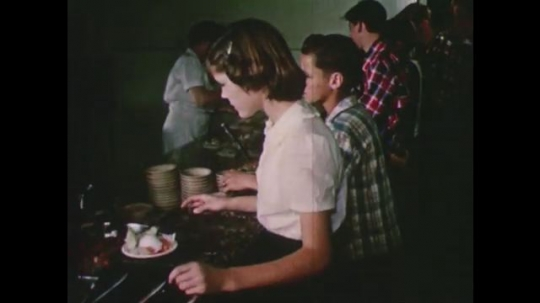 United States: 1950s: Children get food in canteen. Men eat sandwiches at work. Men eat in canteen.