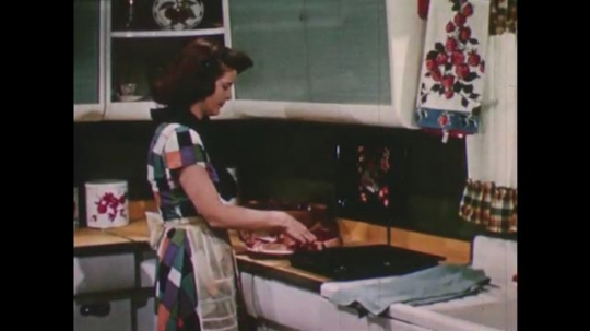 United States: 1950s: Lady puts steak on grill. Lady puts steak in oven.