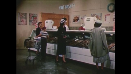 United States: 1950s: lady looks at meat in supermarket. Meat sliced with knife .