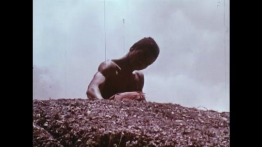 MADAGASCAR: 1970s: man sharpens knife on rock. Man buys girl. Girl runs to rock.