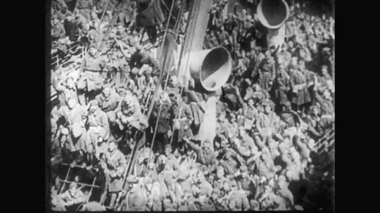 UNITED STATES: 1910s: soldiers wave from deck of ship. People wave and cheer as soldiers arrive by ship.