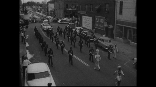 UNITED STATES: 1950s: band marches along street.