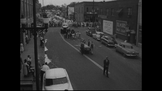 UNITED STATES: 1950s: people carry coffin in street parade.