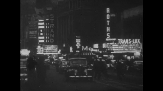 UNITED STATES: 1910s: lights in city street at night during war. Movie star wears uniform.