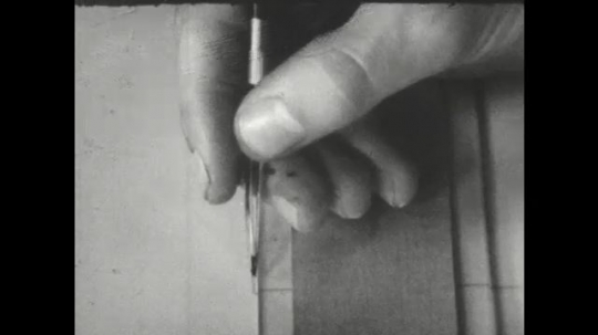 UNITED STATES: 1960s: hand draws line on paper. Eraser corrects mark.