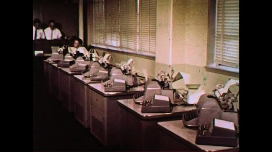 UNITED STATES 1960s: Typewriters in an office automatically types out flight plans for planes.