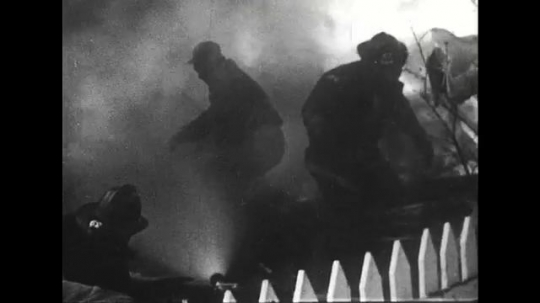 ALASKA 1960s: Firefighters try to fight off a house fire.