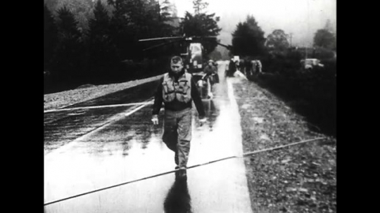 ALASKA 1960s: Relief workers work as a team to transport goods.
