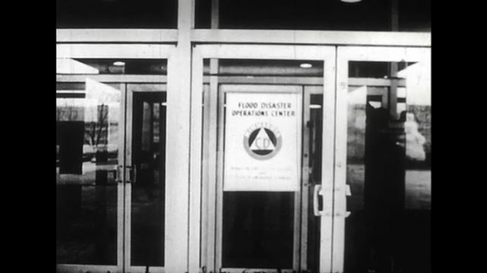 ALASKA 1960s: In a government office, a disaster plan is discussed as a radio announcer broadcasts.