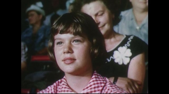 UNITED STATES 1950s: Close up of girl in audience / Elephant pulls float in circus ring.