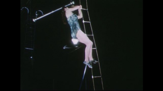 UNITED STATES 1950s: Woman climbs up ladder at circus, stands on trapeze / Long shot of woman swinging on trapeze.