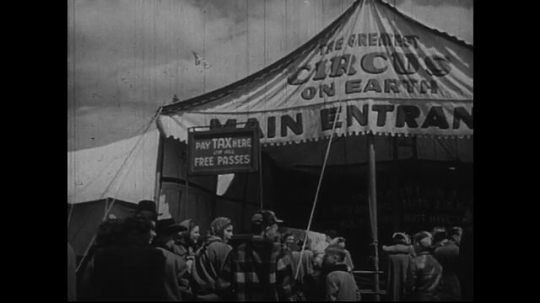 UNITED STATES 1950s:Spectators stand by the circus side show entrance while waiting to enter.