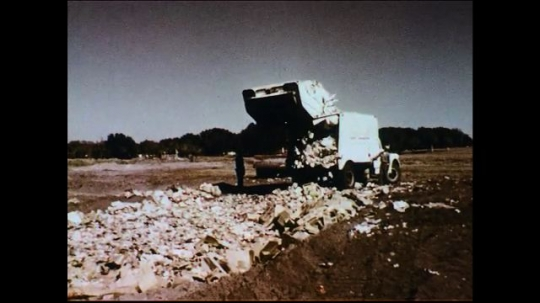 UNITED STATES 1950s: A garbage truck dumps its trash into a wasteland.