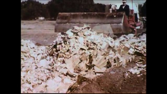 UNITED STATES 1950s: Garbage collected at the municipal dump is buried.