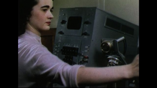 UNITED STATES 1950s: Woman removes phone receiver from machine / New receiver placed on machine / Men in lab / Man looks closely at piece of equipment.